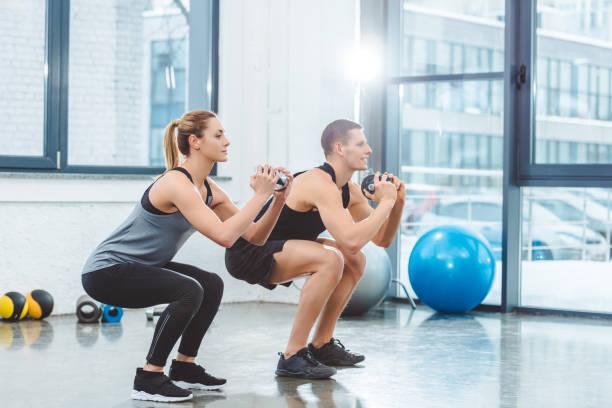 pareja joven deportivo sosteniendo pesas y hacer ejercicio sentadilla en el gimnasio - agacharse fotografías e imágenes de stock