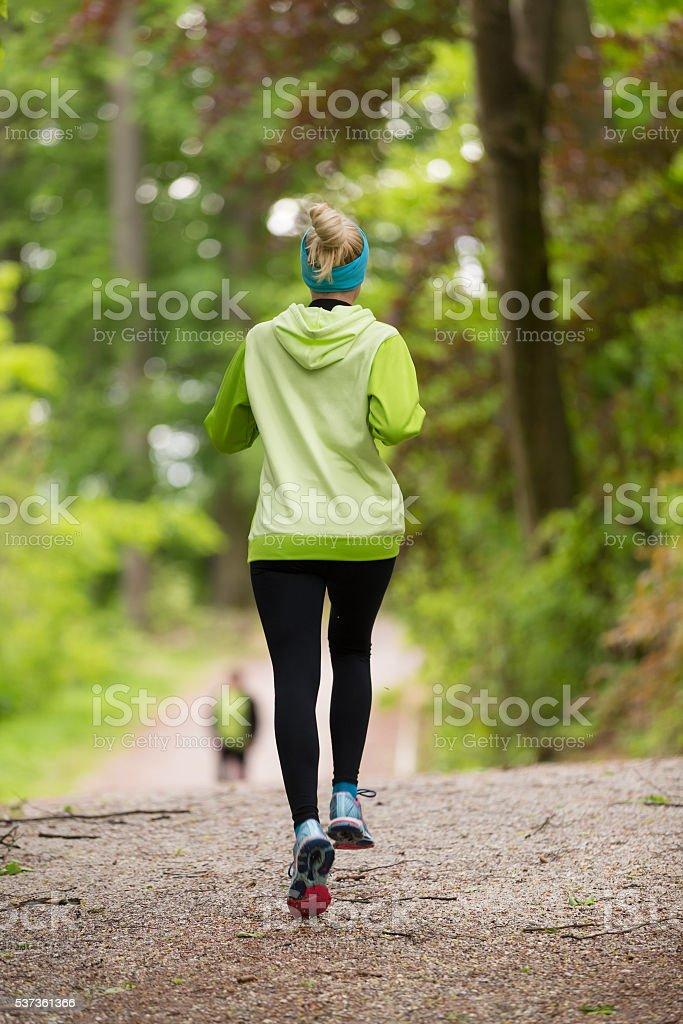 Sportliche junge weibliche Läufer im Wald. Lizenzfreies stock-foto