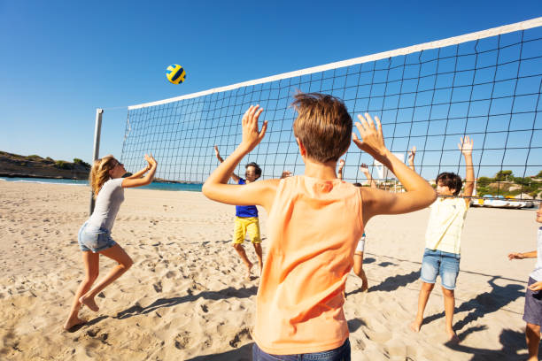 Sporty young girl passing volleyball over the net stock photo