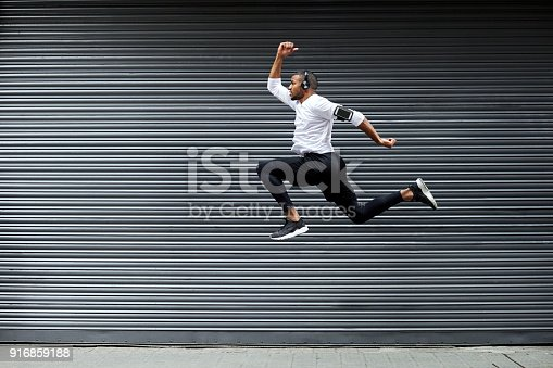Full length of determined young man jumping against shutter. Side view of fit male jogger is exercising in mid-air. He is wearing sports clothing.