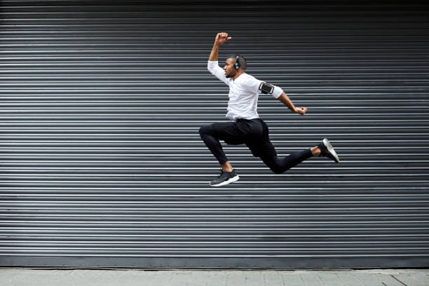 sporty young man jumping against shutter - mid air stock pictures, royalty-free photos & images