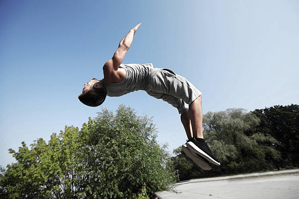 sporty young man jumping in summer park stock photo