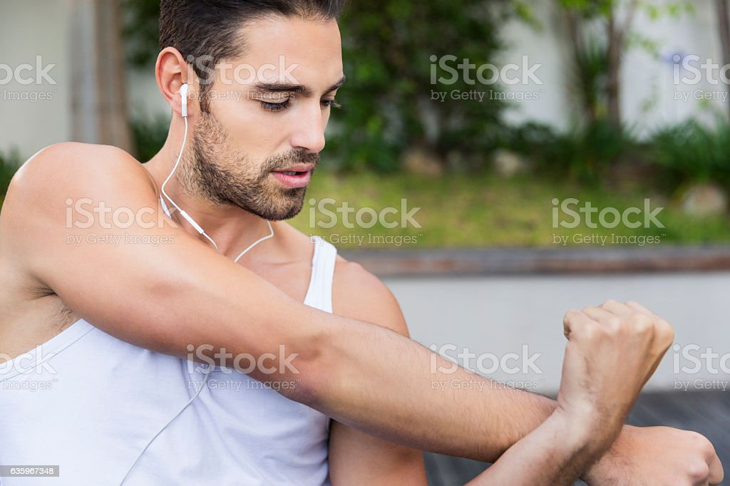 Sporty young man stretching arms in backyard stock photo
