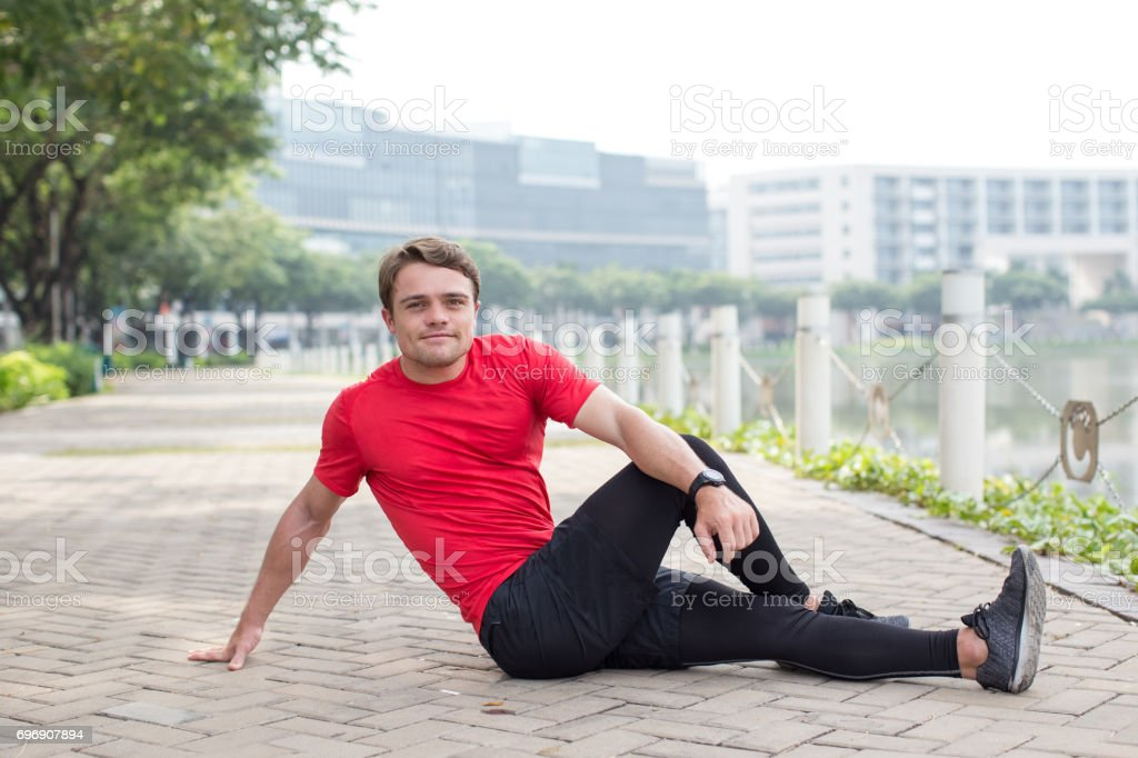 Sporty Young Man Stretching Body on Pavement stock photo
