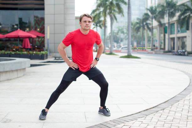 sportlicher junger mann dehnung bein im freien - druck strumpfhosen stock-fotos und bilder