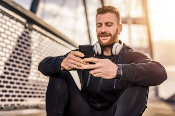 Sporty young man using phone on a bridge. stock photo