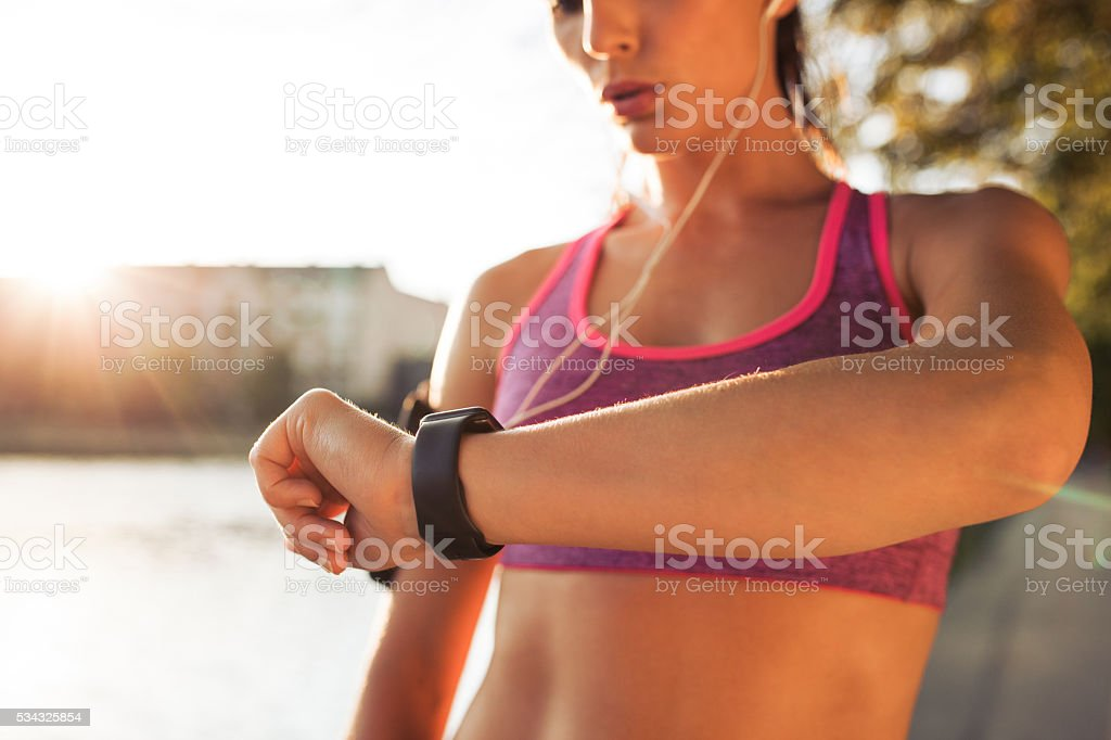 Sporty young woman checking pulse stock photo