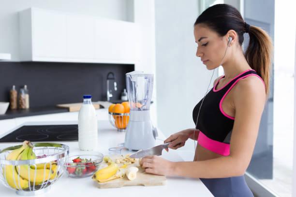 Sportliche junge Frau schneiden Banane beim Musikhören in der Küche zu Hause. – Foto