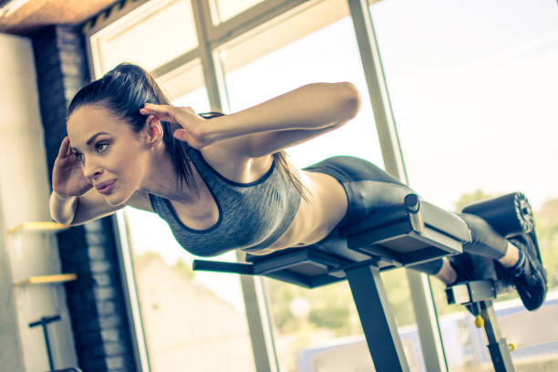 Sporty young woman doing hyperextension exercises on trainer back machine in the gym stock photo