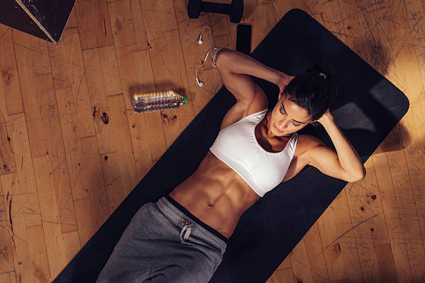 Sporty young woman doing sits-up at gym Sporty young woman lying on yoga mat doing sit-ups in gym. Top view of muscular woman doing abs crunches. abdominal muscle stock pictures, royalty-free photos & images