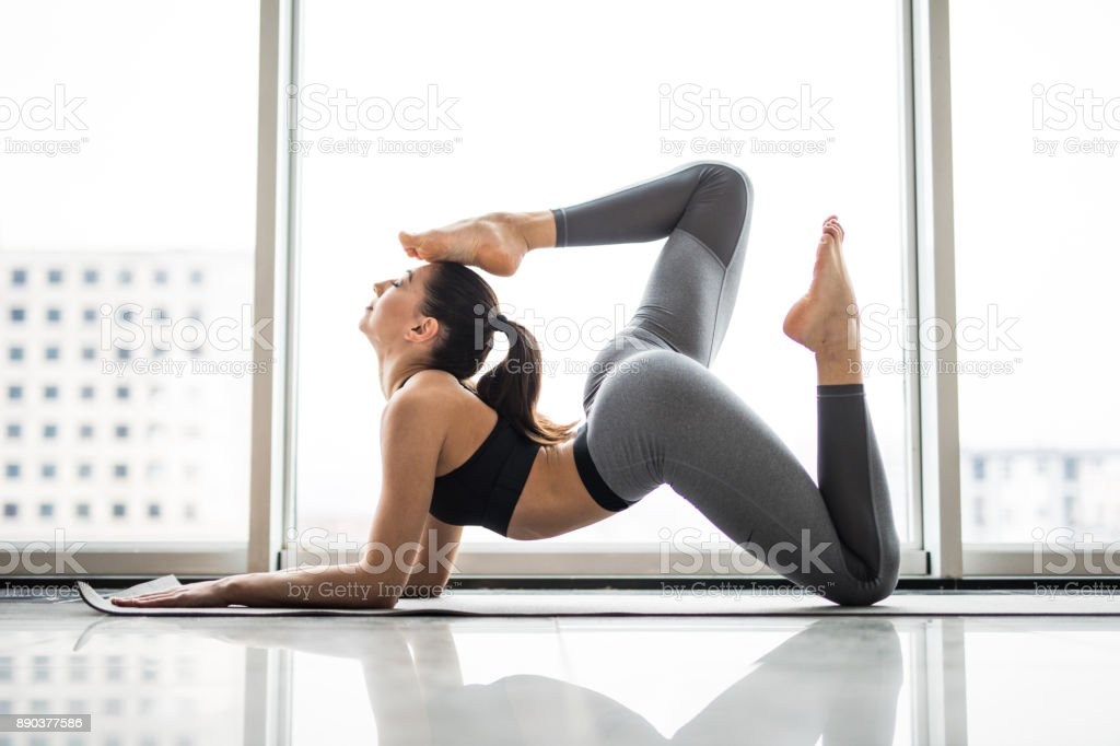 Sporty young woman doing yoga practice against panoramic windows stock photo