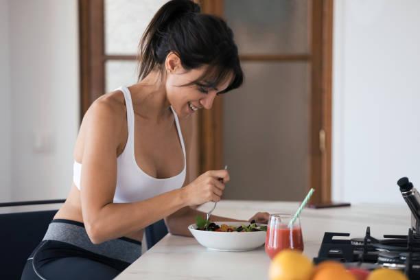 Sportliche junge Frau isst Salat und trinkt Fruchtsaft in der Küche zu Hause. – Foto
