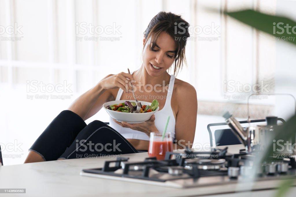 집에서 부엌에서 샐러드를 먹고 과일 주스를 마시는 스포티 한 젊은 여자. - 로열티 프리 가냘픈 스톡 사진
