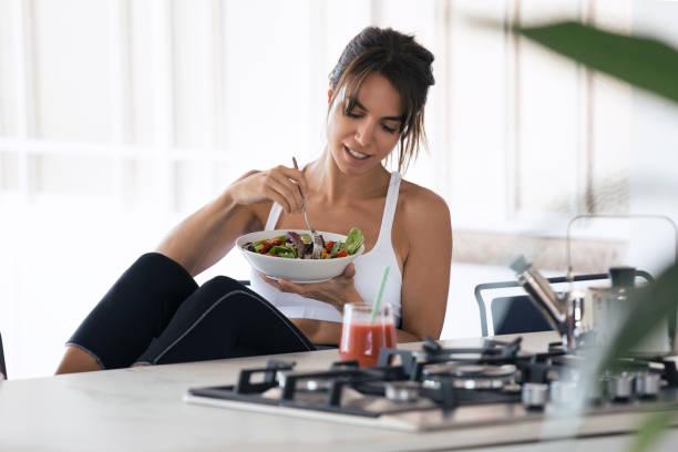 在家裡的廚房裡吃沙拉和喝果汁的年輕女子。 - 健康飲食 個照片及圖片檔