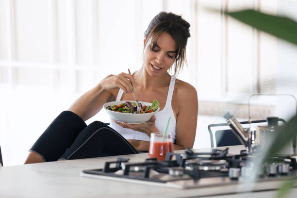sporty young woman eating salad and drinking fruit juice in the kitchen at home. - healthy food imagens e fotografias de stock