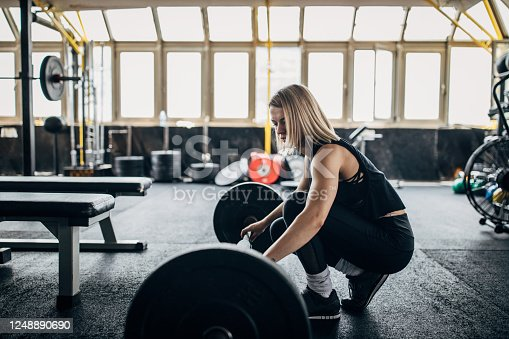 One beautiful fit young woman exercise with barbell in the gym.