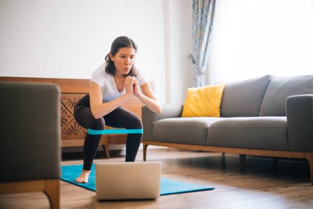 저항 밴드와 집에서 운동 하는 스포티 한 젊은 여자 스톡 사진
