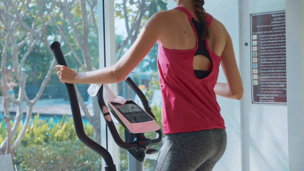 sporty young woman exercising on step machine at the condo gym - ellipse stock photos and pictures