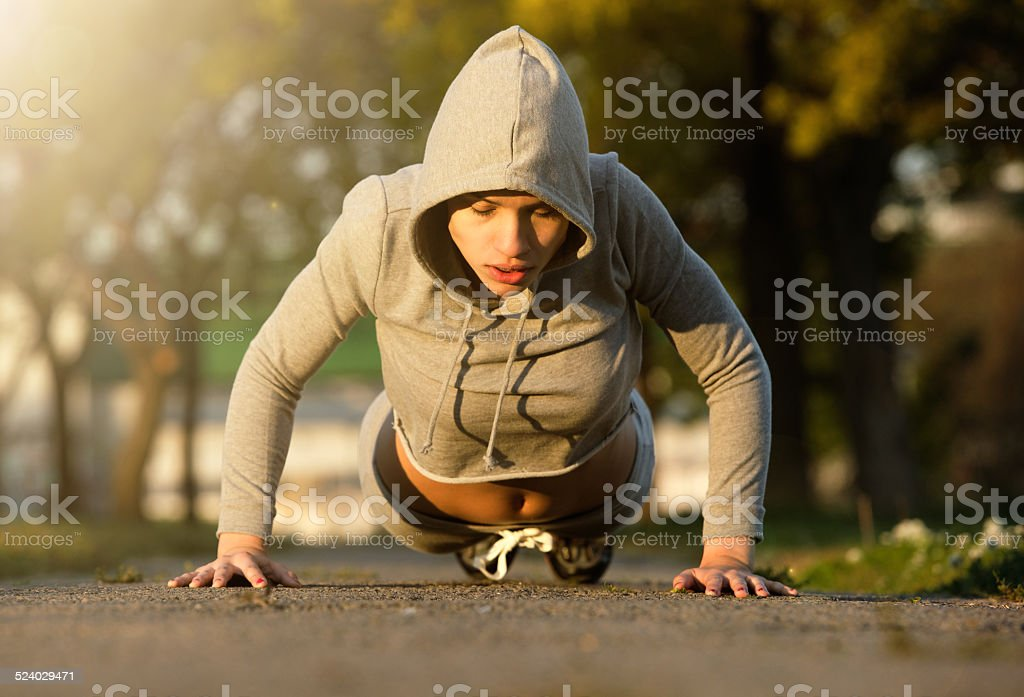 Sporty young woman exercising outdoors stock photo