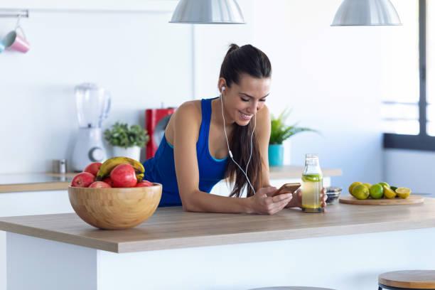 Sportliche junge Frau, die Musik mit dem Handy nach dem Training in der Küche zu Hause hört. – Foto