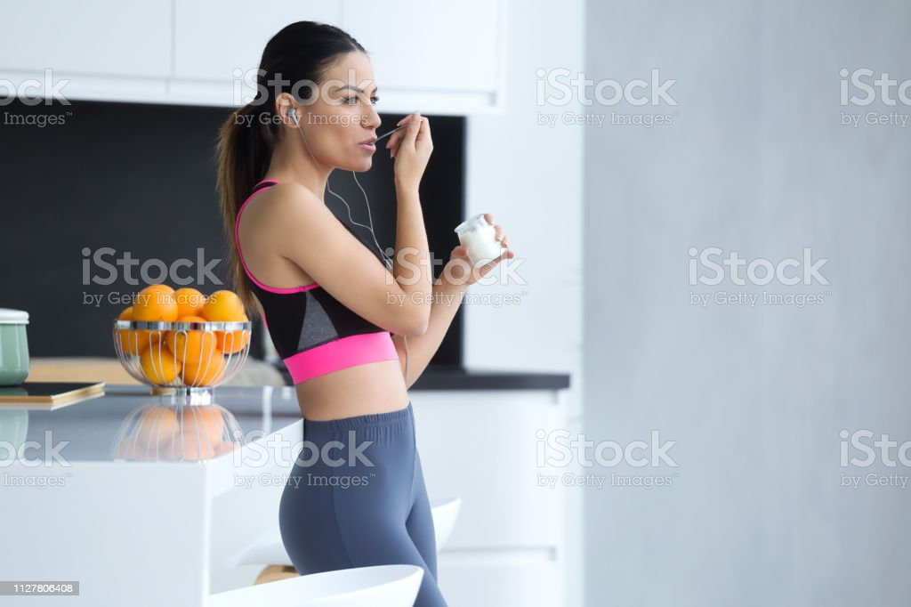 Sporty Young Woman Listening To Music With Mobile Phone While Eating Yogurt In The Kitchen At ...
