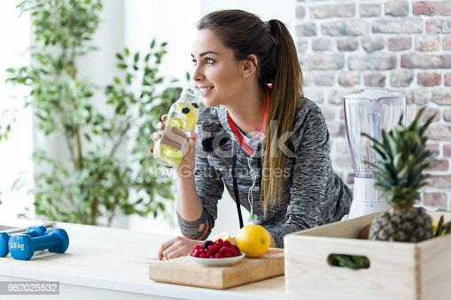 Shot of sporty young woman looking sideways while drinking lemon juice in the kitchen at home.