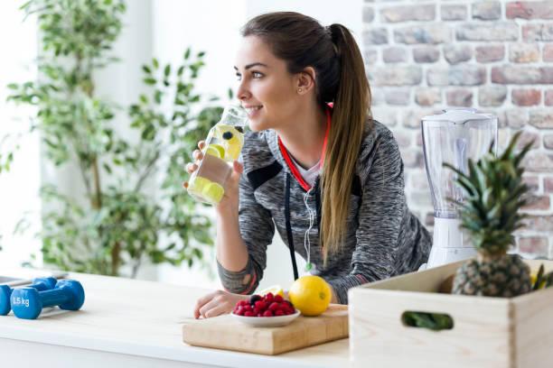 sportowa młoda kobieta patrząc bokiem podczas picia soku z cytryny w kuchni w domu. - detoks zdjęcia i obrazy z banku zdjęć