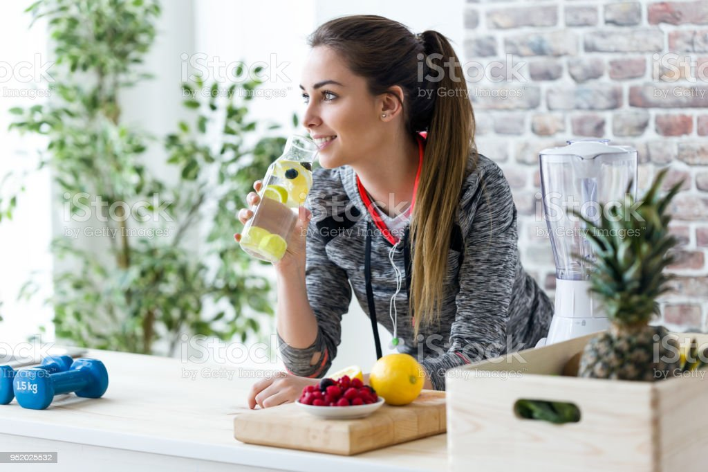 Sporty young woman looking sideways while drinking lemon juice in the kitchen at home. stock photo