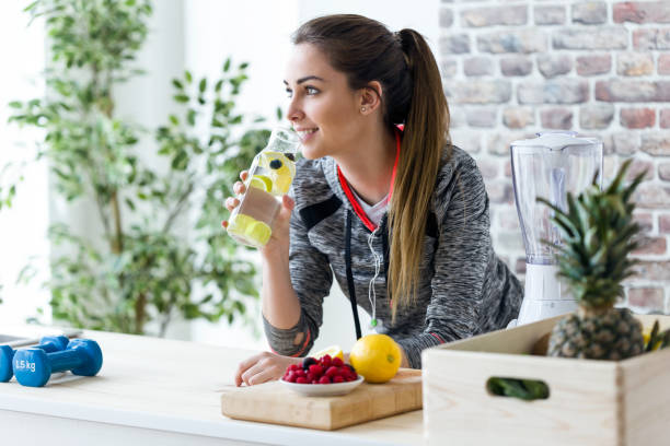sporty young woman looking sideways while drinking lemon juice in the kitchen at home. - healthy food imagens e fotografias de stock