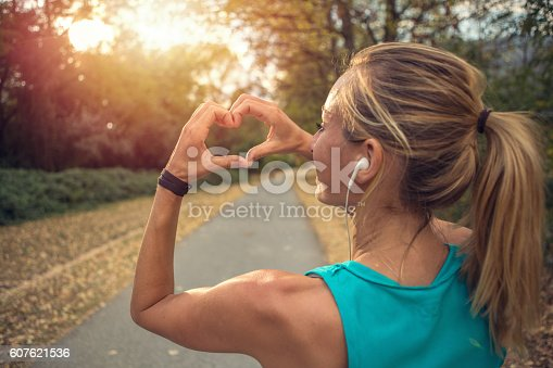 Beautiful and sporty young woman makes a heart shape finger frame after jogging outdoors. Sunset light on the vegetation.
