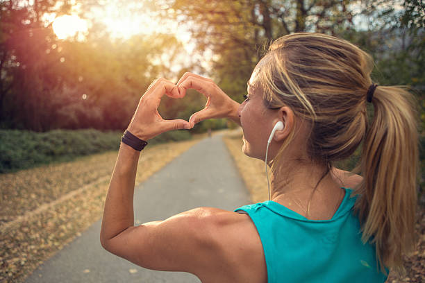 sporty young woman makes heart shape finger frame at sunset - conceptual symbol stock pictures, royalty-free photos & images