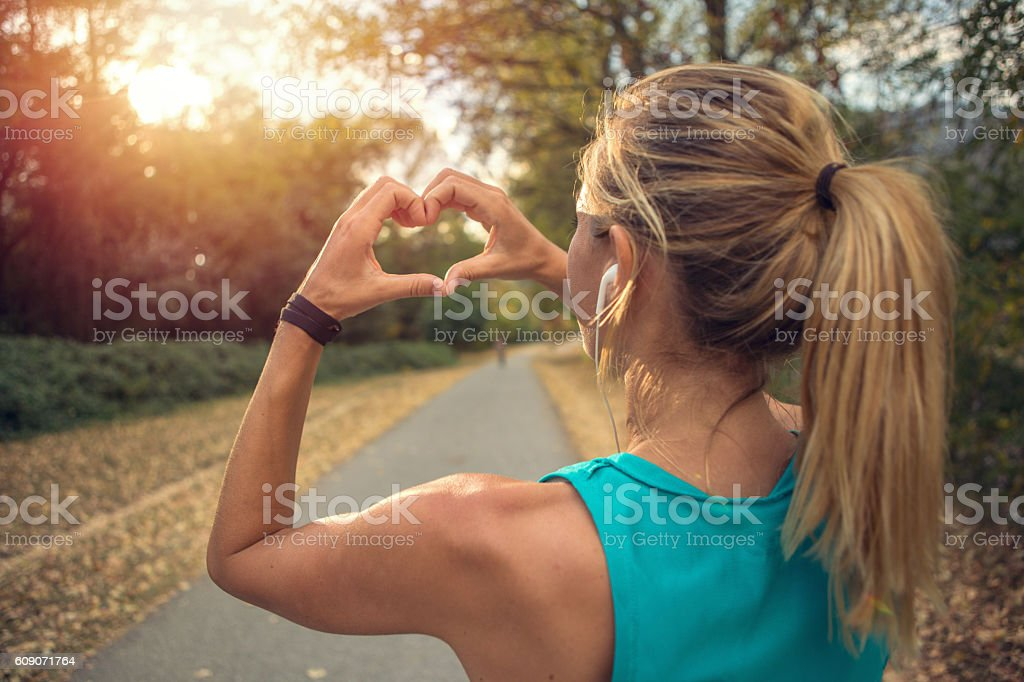 Sporty young woman makes heart shape finger frame at sunset – Foto