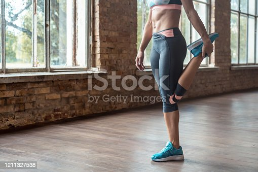 Sporty young woman professional yoga fitness coach trainer stretch leg warmup before training keep fit morning exercise practice workout modern gym fitness studio healthy lifestyle concept copy space