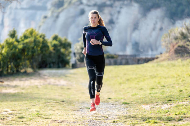 sportliche junge frau läuft auf dem berg in wunderschöner natur. - joggerin stock-fotos und bilder
