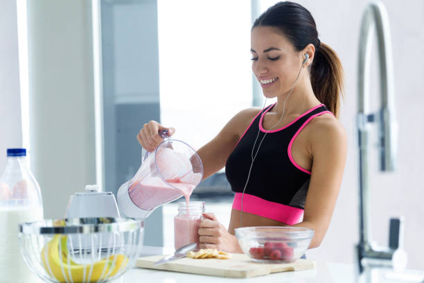 Sporty young woman serving strawberry smoothie in a glass jar in the kitchen at home. Shot of sporty young woman serving strawberry smoothie in a glass jar in the kitchen at home. blender stock pictures, royalty-free photos & images
