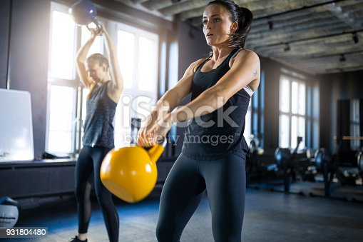 Young woman and friend swinging kettlebells in gym. Determined female athletes are exercising at health club. They are in sportswear.