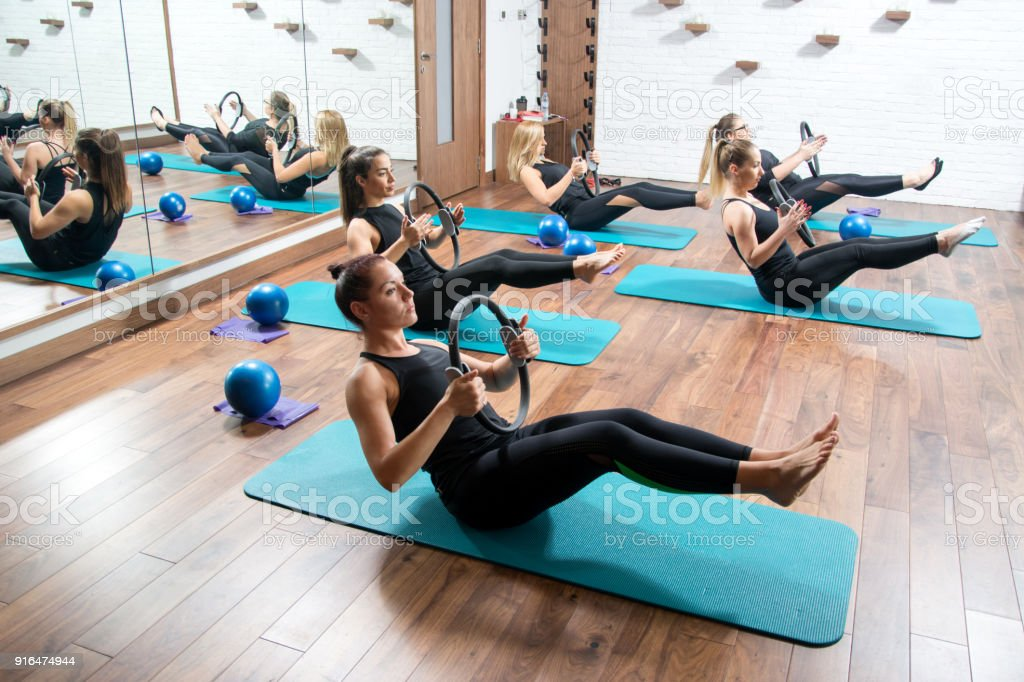 Sporty young women with exercising rings in fitness studio. stock photo