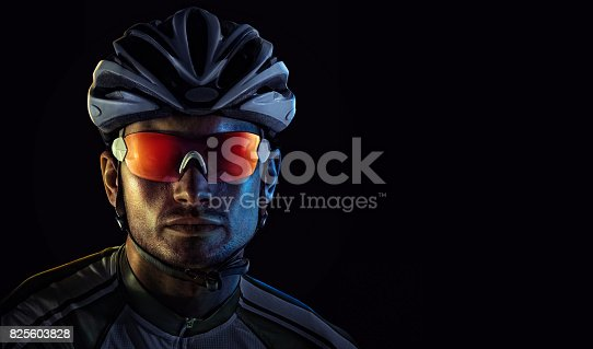 istock Spost background with copyspace. Cyclist. Dramaticcolorful close-up portrait. 825603828
