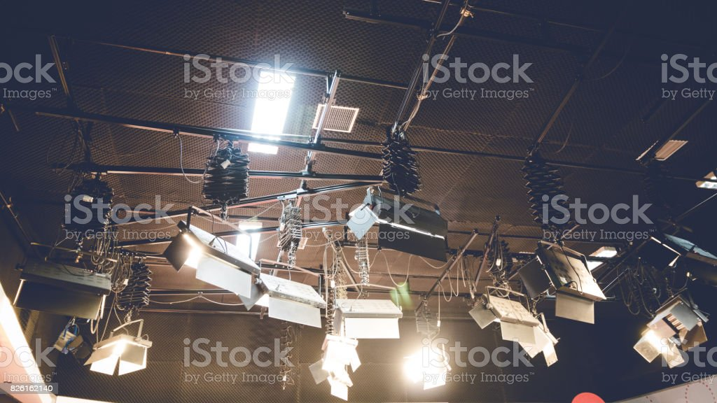 Spot light glowing on studio ceiling background. Illuminated lamp in...