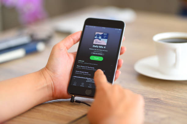 Spotify on iPhone 6 İstanbul, Turkey - August 28, 2017: Woman using smart phone on a wooden desk. The smart phone is an iPhone 6 plus displaying Spotify app.  iPhone is a touchscreen smartphone developed by Apple Inc. mp3 player stock pictures, royalty-free photos & images