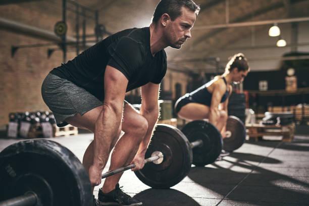 spotive hombre y mujer levantar pesas pesadas - culturismo fotografías e imágenes de stock