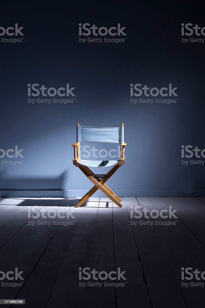 Spotlight on a wooden directors chair made from blue canvas stock photo