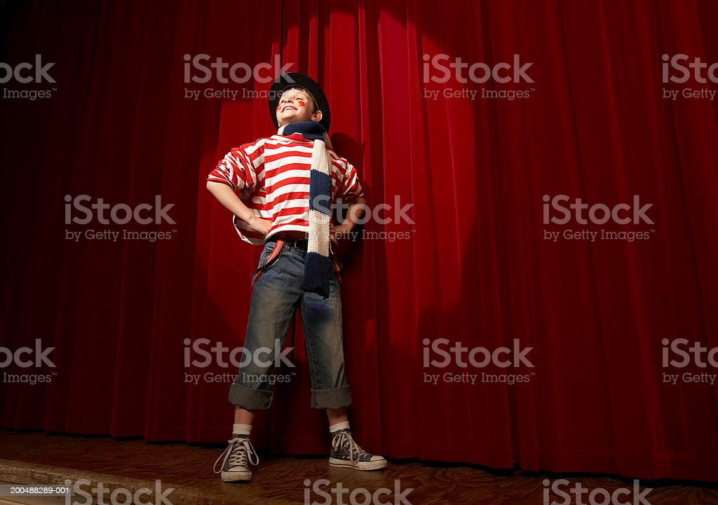 Spotlight on boy (8-10) in clown outfit, hands on hips, low angle view stock photo