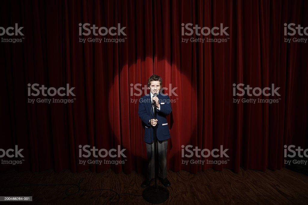Spotlight on on boy (11-13) holding microphone on stage, portrait stock photo