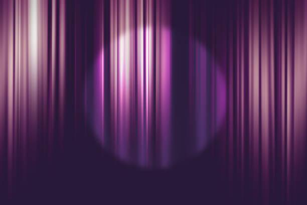 spotlight on purple movie theater curtains background stock photo