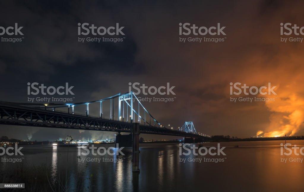 Spotlighted Historical Iron Bridge across the River Rhine at Krefeld Uerdingen View To Duisburg / Night shot stock photo
