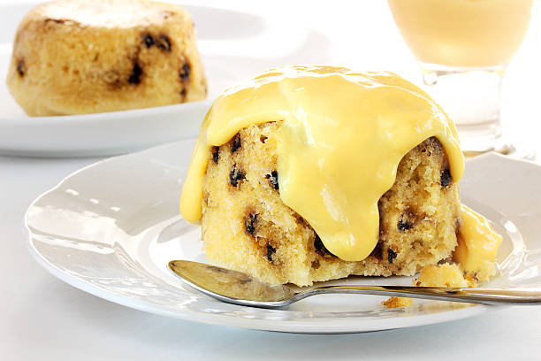 Spotted dick with custard stock photo