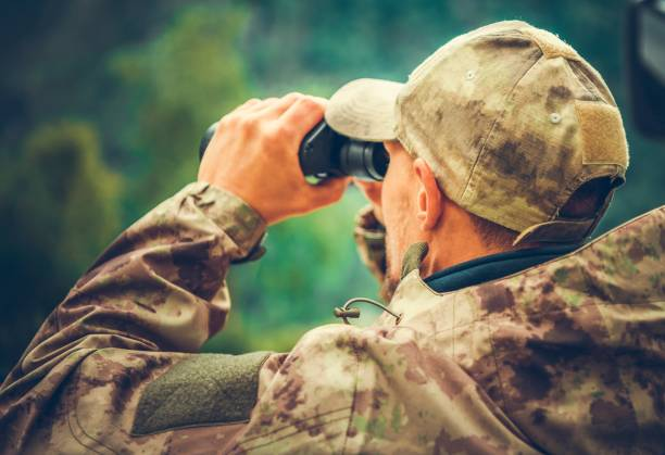 Spotting Game Using Binoculars Caucasian Hunter Spotting Game Using Binoculars. Hunting Season. hunter stock pictures, royalty-free photos & images