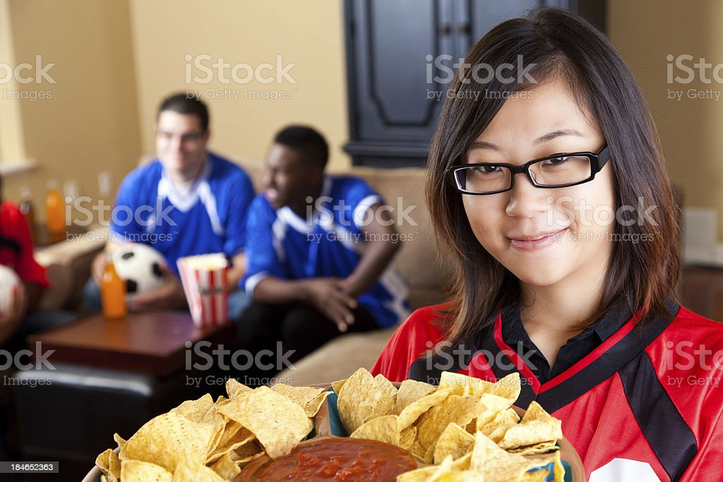 Spouse or girlfriend holding snacks for guys watching soccer game royalty-free stock photo