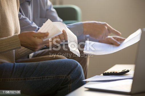 istock Spouses manage family budget check bills cheques closeup cropped image 1158702105
